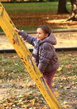 Smiling girl mounting climbing frame Stock Photography