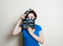 Smiling girl with movie clapper on white background Stock Photography