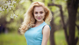 Smiling girl natural beauty, lovely female walking spring nature, portrait of young lovely woman in spring flowers Stock Image