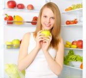 Smiling girl near the refrigerator Lizenzfreies Stockbild