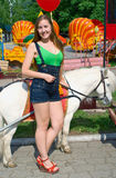 Smiling girl near to a white pony Royalty Free Stock Images