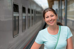 Smiling girl near the the train royalty free stock images