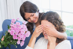 Smiling girl offering flowers to her mother Stock Photos