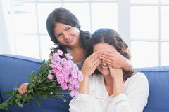 Smiling girl offering flowers to her mother Stock Image