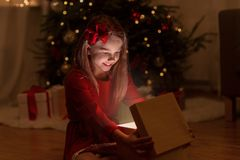 Smiling girl opening christmas gift at night stock photo