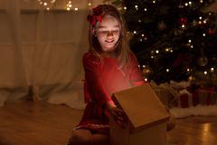 Smiling girl opening christmas gift at night stock photography
