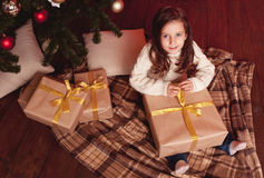 Smiling girl opening christmas presents. Cute kid girl 4-5 year old opening christmas presents in room. Wearing trendy knitted sweater. Sitting on wooden floor Royalty Free Stock Photo