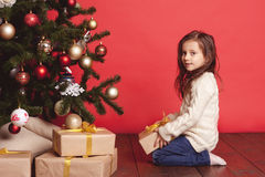 Smiling girl opening christmas presents over red. Cute kid girl 4-5 year old opening christmas presents in room over red. Wearing trendy knitted sweater. Sitting Royalty Free Stock Photography