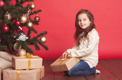 Smiling girl opening christmas presents over red. Cute kid girl 4-5 year old opening christmas presents in room over red. Wearing trendy knitted sweater. Sitting Stock Images