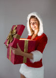Smiling girl opening a gift and looking at the camera Stock Photography