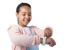 Smiling girl operating her smart watch. Against white background Royalty Free Stock Images