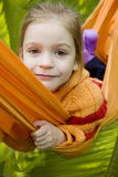 Smiling girl in orange hammock in forest Stock Photos