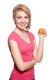 Smiling girl with orange in pink Royalty Free Stock Photography