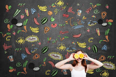 Smiling girl with oranges, fruit sketches, blackboard Royalty Free Stock Image