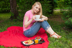 Smiling girl outdoor in the park having picnic Stock Photos