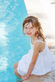 Smiling girl by an outdoor swimming-pool Stock Image