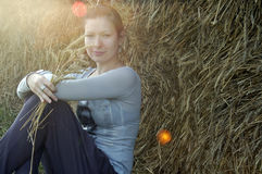Smiling girl outdoors with hay and sun flares Stock Photography