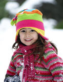 Smiling Girl Outdoors in Winter Clothing. Little smiling girl outdoors playing in the snow Stock Photo