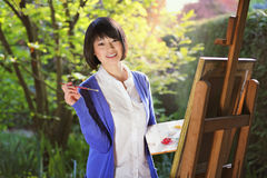 Smiling girl painting a canvas outdoor Royalty Free Stock Image