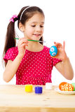 Smiling girl painting easter eggs stock photo