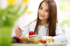 Smiling girl painting Easter eggs Royalty Free Stock Images