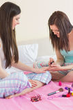 Smiling girl painting her friends nails at sleepover Stock Photos