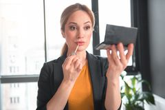 Smiling girl painting mouth at work. Portrait of happy lady rouging lips by lip-gloss while situating in apartment at work. Occupation and glamour concept Stock Photo