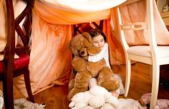 Smiling girl in pajamas hugging teddy bear at self-made house Stock Photo