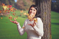Smiling girl palying with autumn leaves Royalty Free Stock Photo