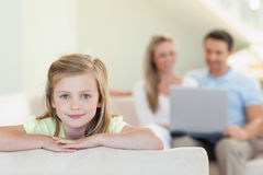 Smiling girl with parents behind her Royalty Free Stock Photo