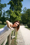 Smiling Girl In Park. Smiling young girl at a park in summer, leaning over a wooden fence with her face turned toward camera Stock Image