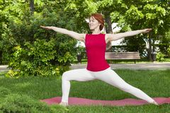 Smiling girl in the park exercise on the yoga mat, high lunge. Portrait stock photos