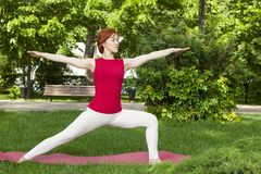 Smiling girl in the park exercise on the yoga mat, high lunge. Portrait royalty free stock photography