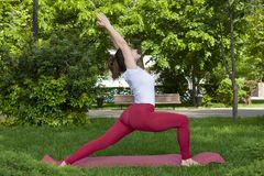 Smiling girl in the park exercise on the yoga mat, high lunge. Portrait royalty free stock photos