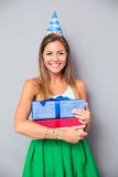 Smiling girl in party hat holding gift boxes Stock Images