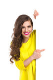 Smiling Girl Peeking And Pointing Royalty Free Stock Photo