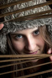 Smiling girl peeking through window blinds. A smiling girl with a fur hat peeking through window blinds Stock Photo