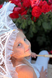 Smiling girl peeks out from under the lace parasol stock photo