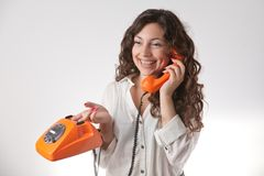 Smiling girl with phone. The smiling girl with orange ancient phone Royalty Free Stock Image