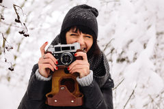 Smiling girl photographed on a camera in winter Royalty Free Stock Photography