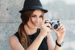 The smiling girl photographs with digital camera. Royalty Free Stock Photography