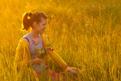 Smiling girl picking flowers on the meadow. Cute happy teenage girl picking flowers on the meadow on sunny spring day Stock Photos