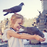 Smiling girl with pigeon on the head Royalty Free Stock Images