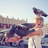 Smiling girl with pigeon on the head and the arms. In old town square Royalty Free Stock Images