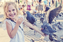 Smiling girl with pigeons on the arm. In old town square Stock Photos