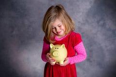 Smiling girl with piggy bank Stock Photos