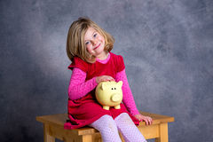 Smiling girl with piggy bank Royalty Free Stock Photos