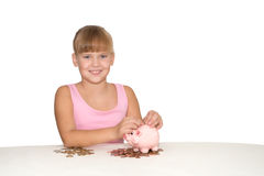 Smiling girl with piggy bank  on teh table isolated Royalty Free Stock Images