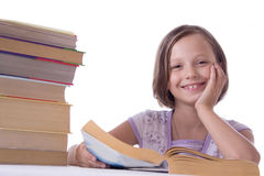 Smiling girl with pile of books Stock Photo