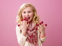 Smiling girl on pink background eating raspberries on fingers Stock Photos